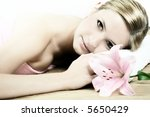 a wellness beauty portrait of a young woman with a flower - stock photo