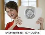 Attractive young woman holds a bathroom scale up while smiling at the camera. Horizontal shot. - stock photo
