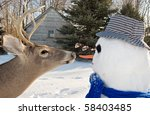 deer going after snowman's nose - stock photo