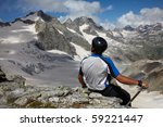 Man in helmet looking to a mountain peak - stock photo