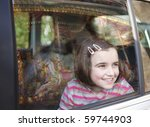 girl smiling and looking out of car window at fairground ride with reflection of carousel in glass - stock photo