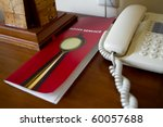 Desk of a hotel guest with room service list and telephone - stock photo