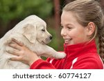Little girl with a Golden retriever puppy - stock photo