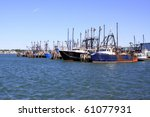 docked fishing boats in a harbor after returning with the catch of the day - stock photo
