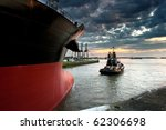 Tug boat taking out the ship from the harbor - stock photo