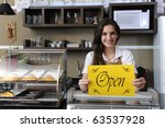 Small business: Happy owner or waitress of a cafe showing open sign - stock photo