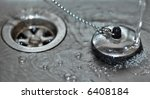 Macro shot of a plug in a sink with running water and water bubbles - stock photo