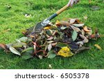 Sweeping up leaves in the Autumn. - stock photo