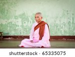 YANGON, MYANMAR - JAN 28: Buddhist nun praying for the full moon festival, Shwedagon Pagoda, January 28, 2010 in Yangoon, Myanmar - stock photo