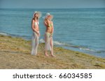 two women in bikinis standing on beach in white hats - stock photo