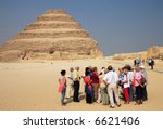 Tourists and Ancient step pyramid of Djoser (Zoser) at Saqqara, Egypt - Editorial - stock photo