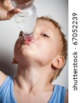 Quench thirst. The boy is drinking mineral water from plastic bottle - stock photo