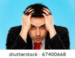 Portrait of a worried businessman, blue background - stock photo