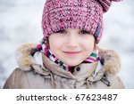 Winter portrait of adorable small girl with blue eyes in pink hat looks into the camera - stock photo