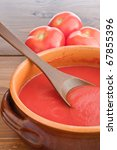 Fresh raw tomato sauce in a terracotta pot on a wooden table - stock photo