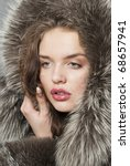 The young beautiful girl with chubby lips in a fur  coat - stock photo