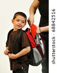 Boy looking back at his backpack as she packs it for school. - stock photo