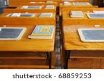 Two rows of  old school house wood desks with chalk tablets and reading books - stock photo