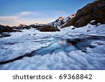 late winter scenery of icy alpine lake with sunrise reflections - stock photo
