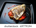 Grilled sea bream fillet on ratatouille with cherry tomato coulis - stock photo