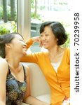 Family portrait of Asian ethnic mature mother enjoy talking with teen daughter - stock photo