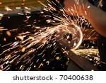Worker cutting metal using angular grinding machine - stock photo