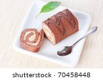Closeup swiss roll with condensed milk cream on ? white plate with spoon and a green leaf - stock photo