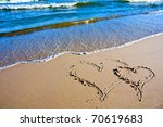 Two hearts drawn on the sand of a beach - stock photo