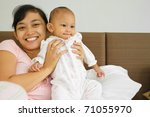 Family portrait of asian ethnic mother holding cute baby girl on bed - stock photo