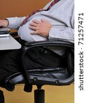 Middle aged man sitting in his office holding his large stomach while working at his desk. Sedentary men with heavy mid sections are more at risk for diabetes, heart attacks and strokes. - stock photo