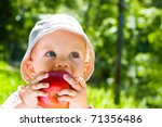 Portrait of beautiful baby boy eating apple on the lawn - stock photo