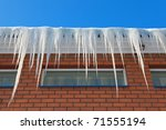 Icicles on the roof of a brick house - stock photo