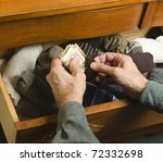 man hiding cash in sock drawer - stock photo
