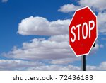 Stop sign against blue cloudy sky - stock photo