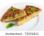 Slices of Spanish omelet or tortilla de patatas on a white plate, garnished with mint leaves - stock photo