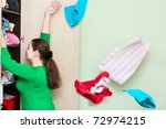 Young caucasian woman throwing a clothes from the wardrobe back. - stock photo