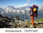 Hiker girl with backpack and ice-axe in a high mountains - stock photo
