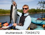 fisherman holding a fresh caught fish - stock photo