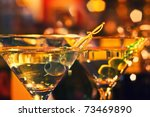 Olive and glass Martini with candle - very small focus - stock photo