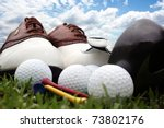 Golf shoes and equipment sitting on grass with a bright blue sky in the background - stock photo