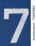 Starting number seven on a blue tartan athletic running track on the stadium. Tartan track is the trademarked all-weather synthetic track surfacing for athletics made of polyurethane - stock photo