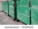 Row of garbage dumpsters are line up in a residential neighborhood. - stock photo