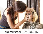A beautiful young girl having makeup applied by a professional artist. - stock photo