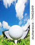 Golf  ball on a tee  against a bright blue sky in the background - stock photo