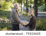 Senior couple walking along the sidewalk looking back at the camera - stock photo
