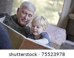 Grandfather reading a book to his grandchild - stock photo
