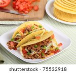 Two tacos with lettuce, tomatoes, cheese on a plate with ingredients in background - stock photo