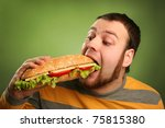 funny guy eating hamburger on green background - stock photo