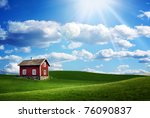 Red 	wooden house on a green field - stock photo