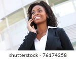 A beautiful african woman on cell phone at work or school - stock photo